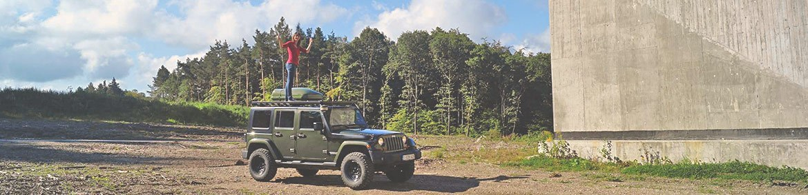 girl standing on very strong and sturdy jeep jk roof rack with cargo box